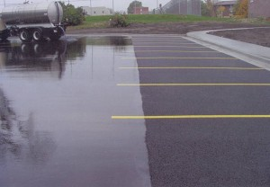 Porous Asphalt, Iowa: A water truck demonstrates how porous pavement at the right drains quickly, while water stands on the conventional pavement at the left. Photo courtesy of NAPA.