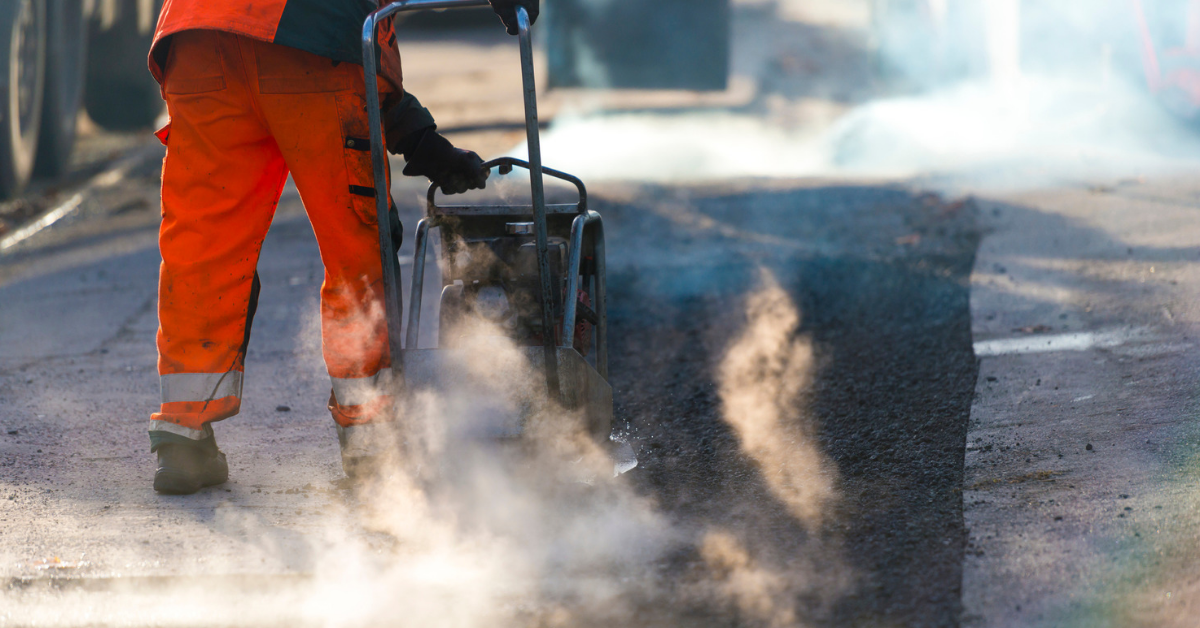 person working on asphalt for a big-box retailers parking lot
